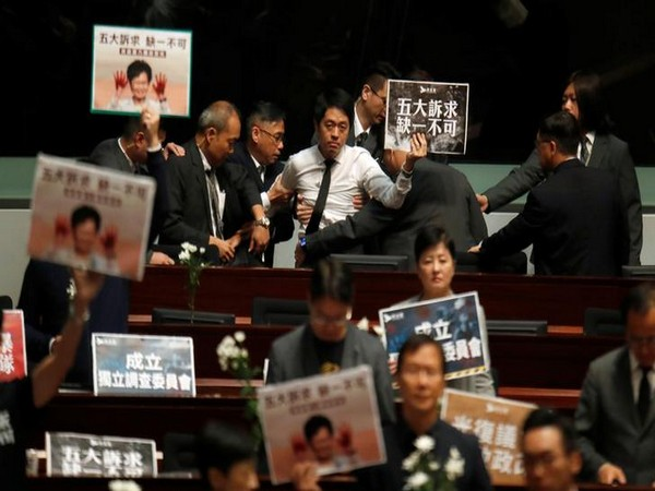 A pro-democracy lawmaker being escorted by security from the Hong Kong Legislative Council on Thursday. Photo/ANI