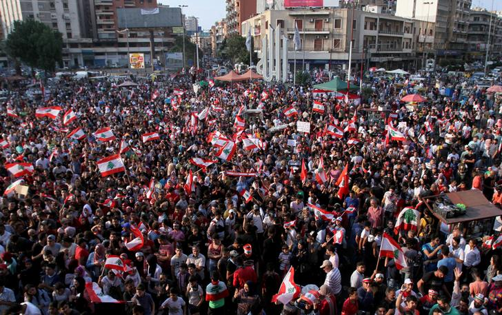 Demonstrators carry national flags during an anti-government protest in Tripoli, Lebanon