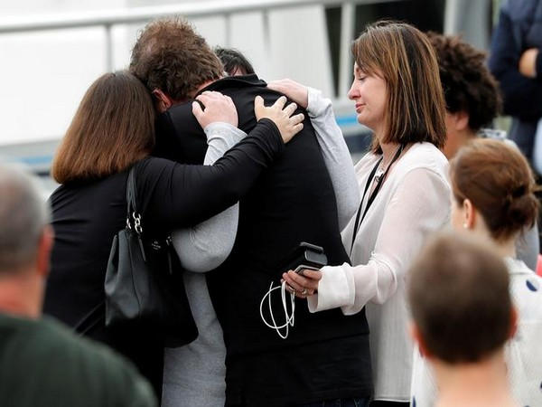 Relatives hug eachother as they wait for rescue mission following the White Island volcano eruption in Whakatane, New Zealand
