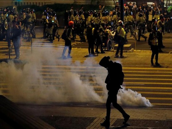 An anti-government demonstrator walks past tear gas on Christmas Eve in Hong Kong on Tuesday. Photo/Reuters