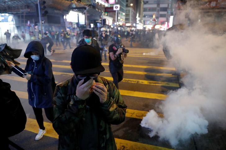 Anti-government protesters react to tear gas during a protest on Christmas Eve at Tsim Sha Tsui in Hong Kong,