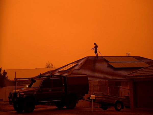 A resident uses a garden hose to wet down the house as high winds push smoke and ash from the Currowan Fire towards Nowra, New South Wales.