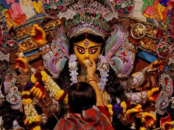 An Idol of goddess Durga being fed 'bhog' by a devotee.