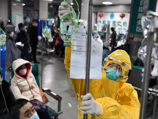 A medical worker in protective suit adjusts a drip bag for a patient at a hospital, following an outbreak of the new coronavirus in Wuhan