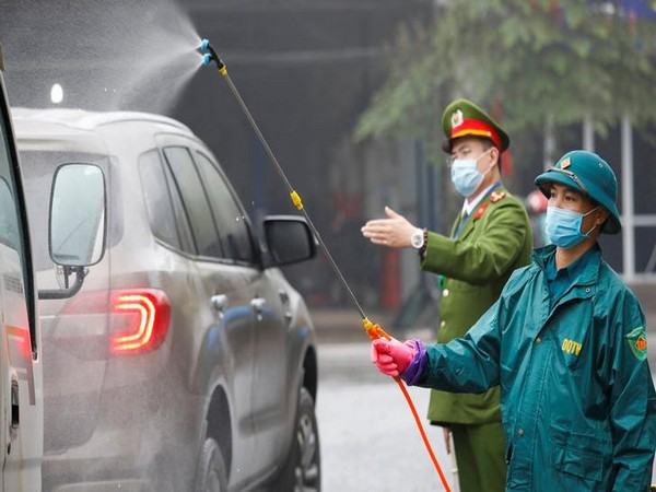 Members of anti-coronavirus team spray chemical into vehicles on a road in Vietnam's Thai Nguyen province