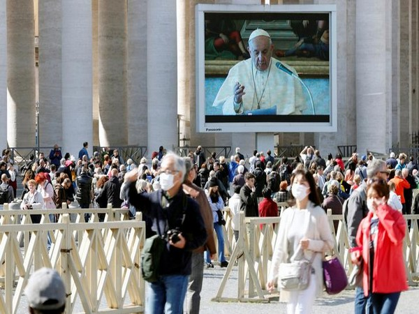 People in face masks walk on St. Peter's Square as Pope Francis delivers his weekly Angelus prayer transmitted via video