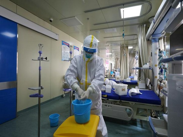 Medical workers in protective suits disinfect an intensive care unit (ICU) ward at a hospital