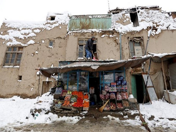 An Afghan man removes snow from his shop during a snowfall in Kabul, Afghanistan