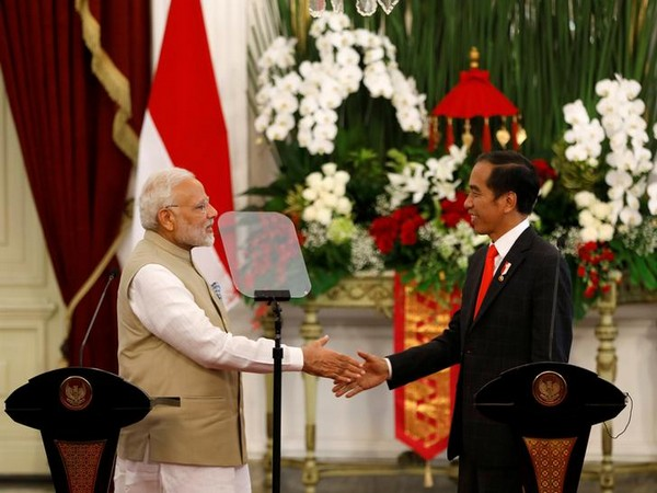 Indian Prime Minister Narendra Modi (L) shakes hands with Indonesia President Joko Widodo after they spoke following their meeting at the presidential palace in Jakarta