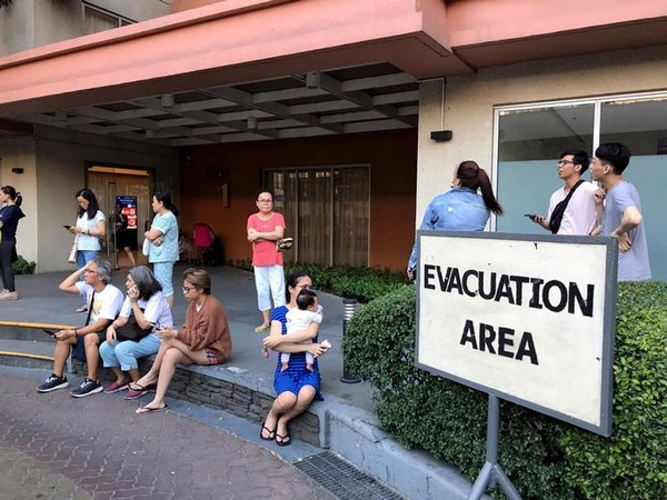 Residents sit outside after being evacuated from the condominium building after an earthquake in Makati City, Philippines (image source: Reuters)