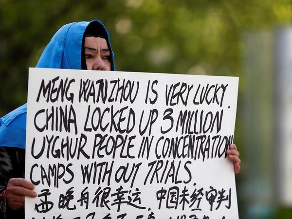 A demonstrator holds a sign protesting China's treatment of Uighur people in the Xinjiang region (Photo: Reuters)