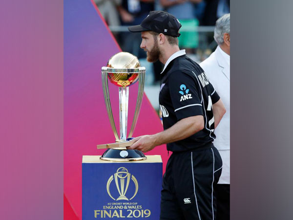 New Zealand's Kane Williamson walking past the World Cup trophy