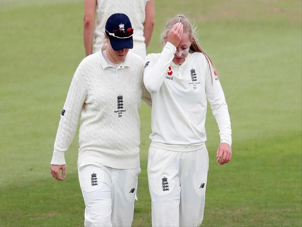 England's Anya Shrubsole (left) taking teammate Sophie Ecclestone (right) off the field after the latter injured her right shoulder