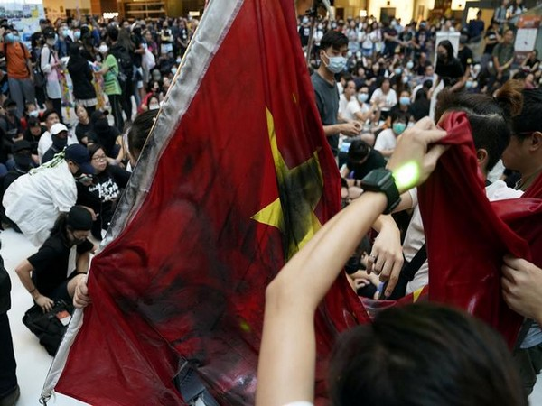 Anti-government protestors vandalise Chinese flag during a rally in Hong Kong on Sunday.