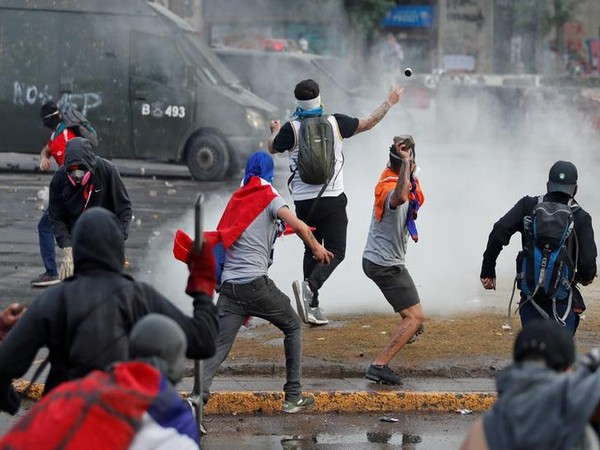Demonstrators throw stones and tear gas canister during a protest in Santiago on Monday. Photo/Reuters