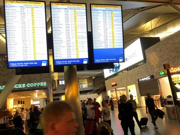 People look on and walk next to a flights information board inside the terminal of Amsterdam's Schiphol airport
