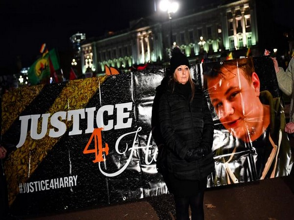Harry Dunn's mother Charlotte Charles poses in front of a banner outside the Buckingham Palace