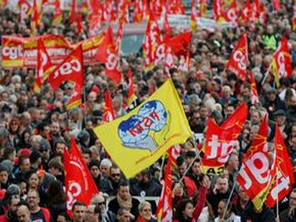 French Labour unions members holding flags attend a demonstration against French government's pensions reform plans in Marseille as part of a day of national strike and protests in France