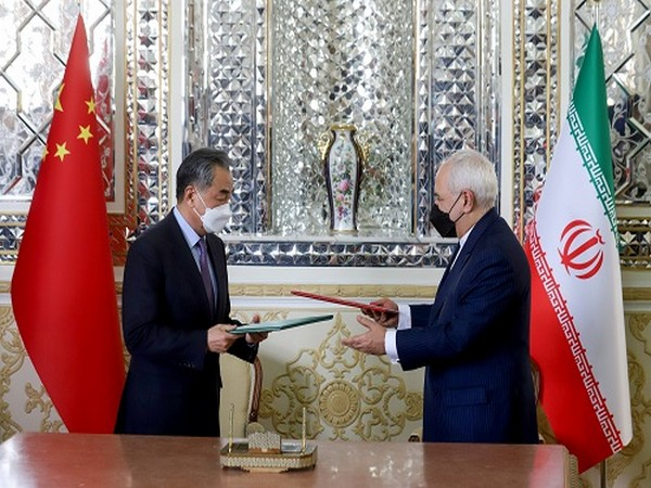 Iran's FM Mohammad Javad Zarif and China's FM Wang Yi exchange documents during the signing ceremony of a 25-year cooperation agreement, in Tehran, Iran March 27, 2021. (Photo Credit: Reuters)