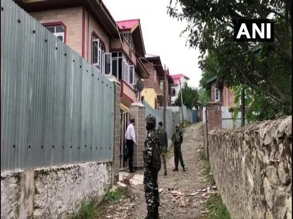 Security personnel outside a house raided by the NIA in Baramulla district on Sunday.