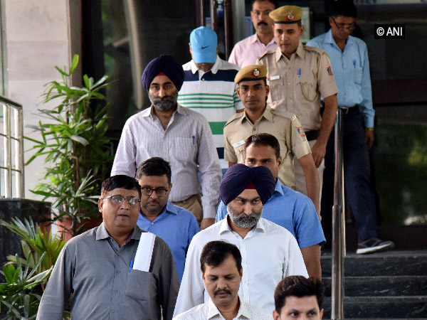 Malvinder Mohan Singh, Shivinder Mohan Singh and 3 other accused coming out of Saket court in New Delhi on Friday. Photo/ANI