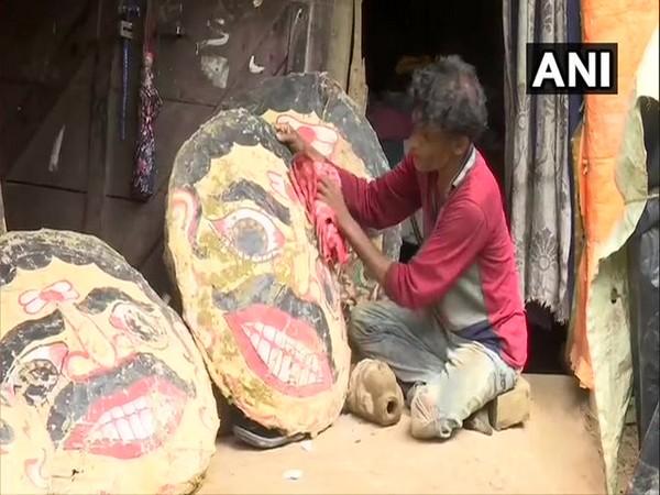 Prakash Bhoi, the artisan, with heads of the effigies on Saturday. photo/ANI