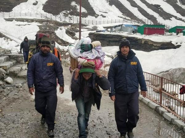 SDRF personnel helping the devotees cross snow-laden paths in Kedarnath. Photo: ANI.