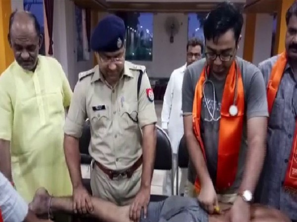 Shamli Superintendent of Police Ajay Kumar tends to Kanwar pilgrims at a medical camp. on Saturday. Photo/ANI