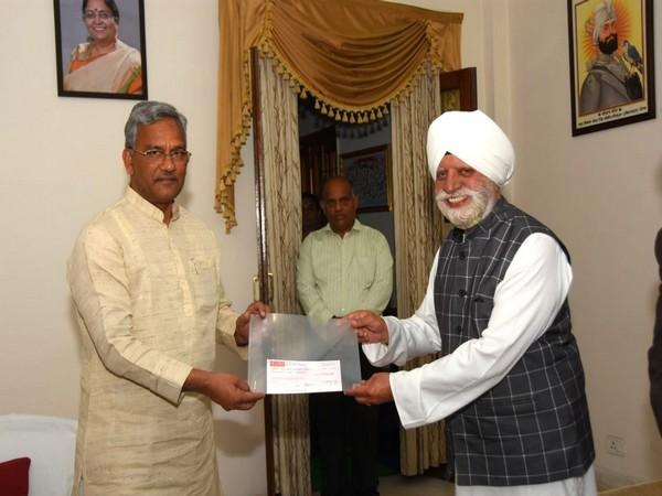 Uttarakhand Chief Minister Trivendra Singh Rawat receiving Rs 50 lakh cheque from Sant Nirankari Mandal member Harbhajan Singh on Monday. Photo/ANI