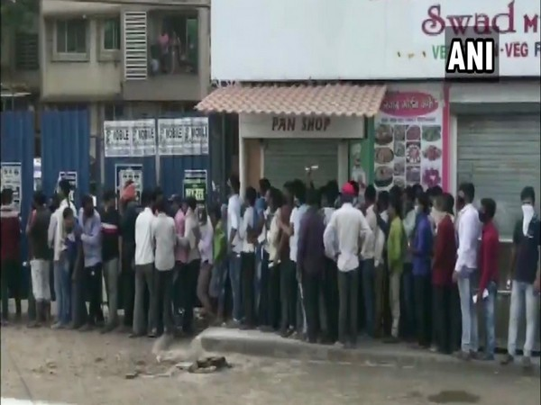 Migrant workers queue outside medical clinics in Dombivli city of Thane.