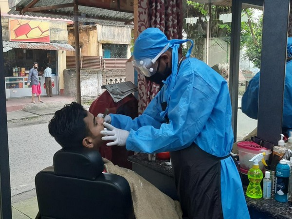 Barber wears PPE while providing service to customer in Siliguri. Photo/ANI
