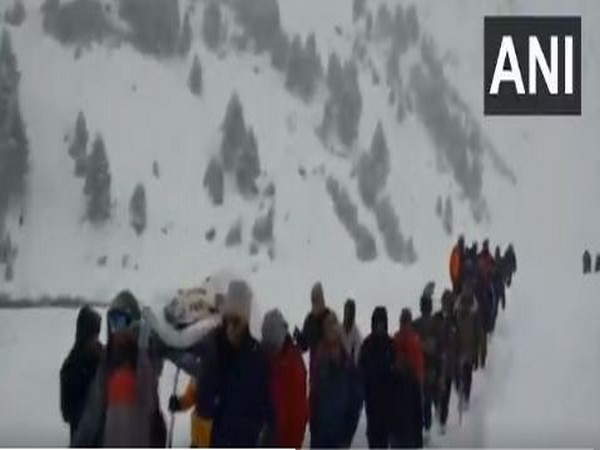 Visual of villagers and police carrying cop in Lahul Spiti. (Photo/ANI)