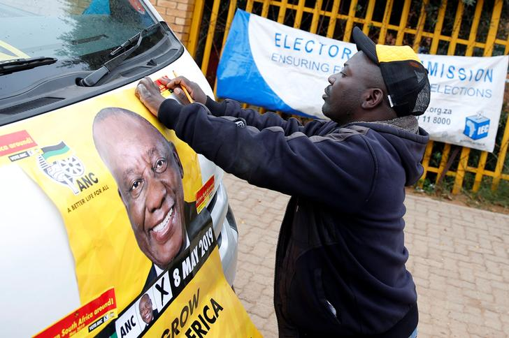 A man places an election poster of President Cyril Ramaphosa on a minibus taxi outside a polling station on Wednesday in Johannesburg, South Africa. (Photo: Reuters)