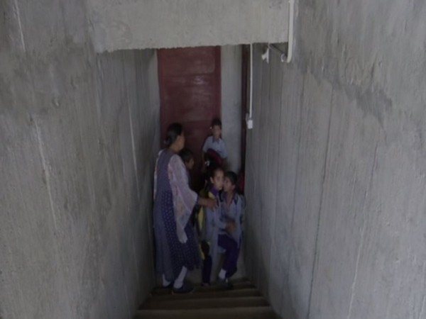 Students and teacher getting inside a bunker that has been constructed at a Government Primary school in Rajouri district