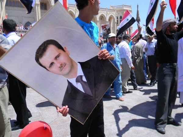 A portrait of President Bashar al-Assad in hands of a protestor