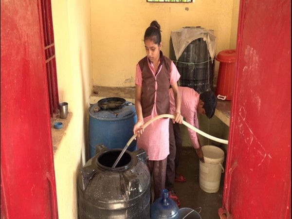 A school girl filling a tank with the rain harvested water at a government school in Agra [Photo/ANI]