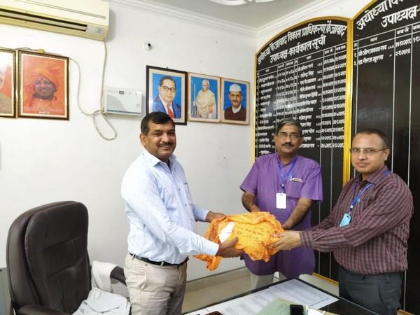 Dr Anil Mishra, member of Ram temple Trust handing over layout of Ram temple to ADA vice chairman Neeraj Shukla ( white shirt) on Saturday. (Picture source: Twitter/Shri Ram Janmbhoomi Teerth Kshetra)