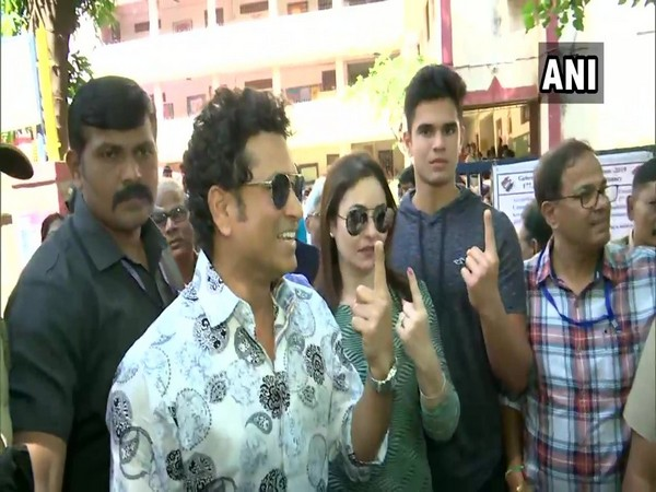 Sachin Tendulkar with wife Anjali and son Arjun, posing outside polling booth.