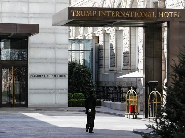 A staff member wears gloves while walking past an entranceway at Trump International Hotel, as Mayor Muriel Bowser declared a State of Emergency due to the coronavirus in Washington, US.