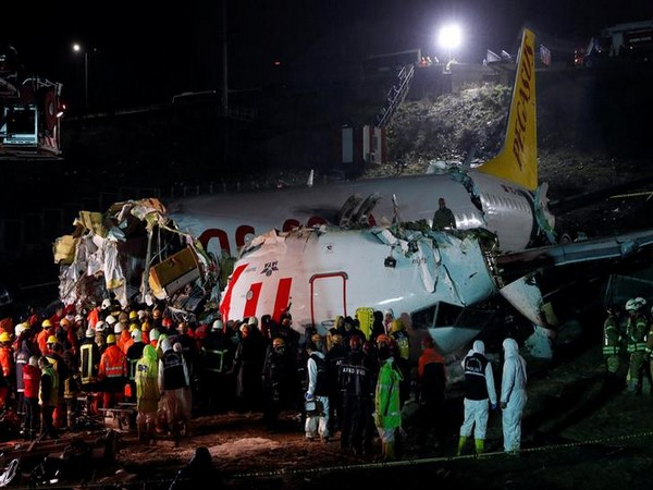 First responders gather around the Pegasus Airlines Boeing 737-86J plane wreckage after it overran the runway during landing and crashed, at Istanbul's Sabiha Gokcen airport.