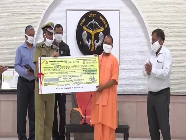 UP Police DGP hands over a cheque of Rs 20 crore to CM Yogi Adityanath in Lucknow on Wednesday. Photo/ANI