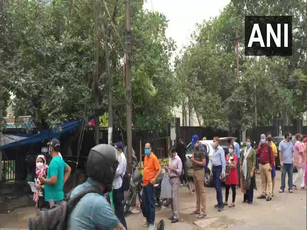 Visual of people standing outside vaccination centre in UP. (Photo/ANI)