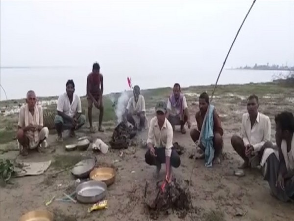 Locals of villages submerged into River Ganga offer special prayers at riverbank. Photo/ANI