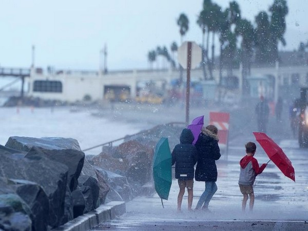 Kids use umbrellas for protection from the crashing waves of a high tide as a winter storm arrives in Oceanside, California