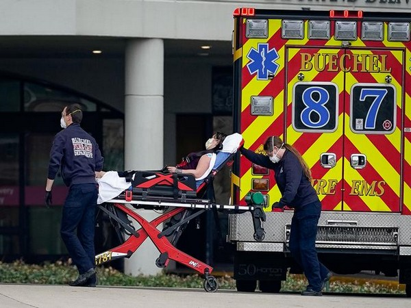 Emergency medical personnel transporting a patient suffering from COVID-19 into the emergency department in Louisville, Kentucky, US, March 24.