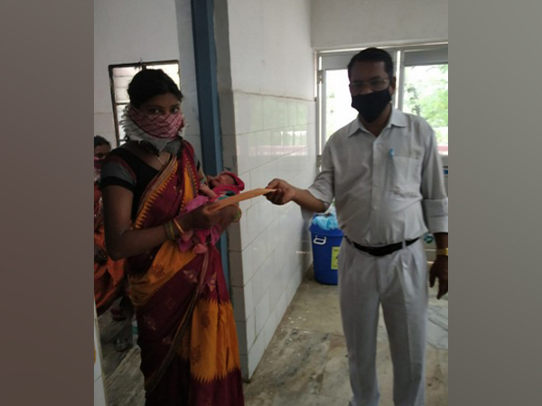 ECoR official giving gift coupon to mother of a baby born on board Shramik Special Train