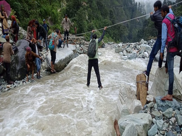 Villagers cross river with ropes as Forest Jeep is currently blocked in Sankri due to landslides. Photo/ANI