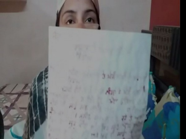 One of the two girls showing the letter written for Presidnet Ram Nath Kovind to seek justice. Photo/ANI