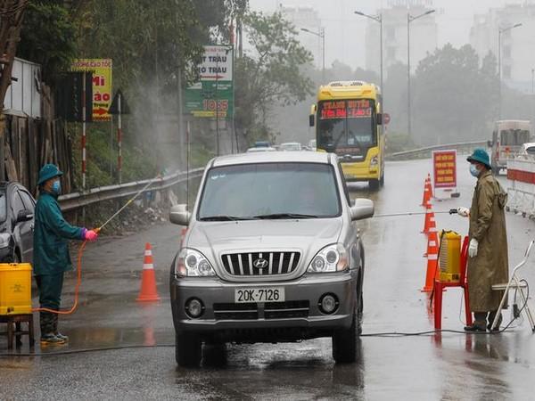 Members of anti-coronavirus team spray chemical in vehicles on a road in Thai Nguyen province in Vietnam.