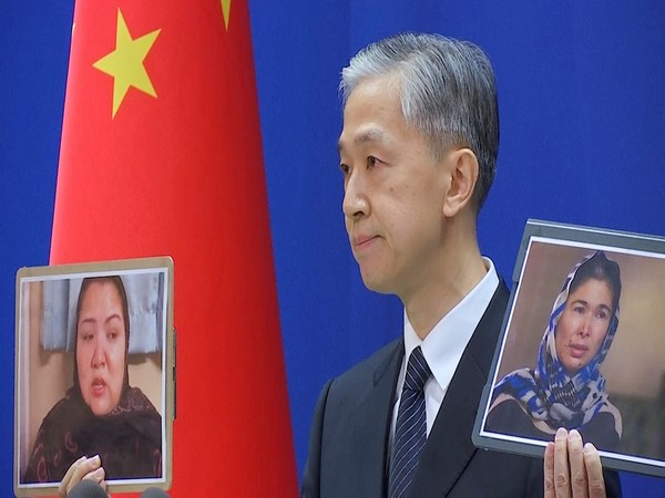 China's Foreign Ministry spokesman Wang Wenbin holding up images of witnesses who described sexual abuse in Xinjiang (Photo Credit - Reuters)